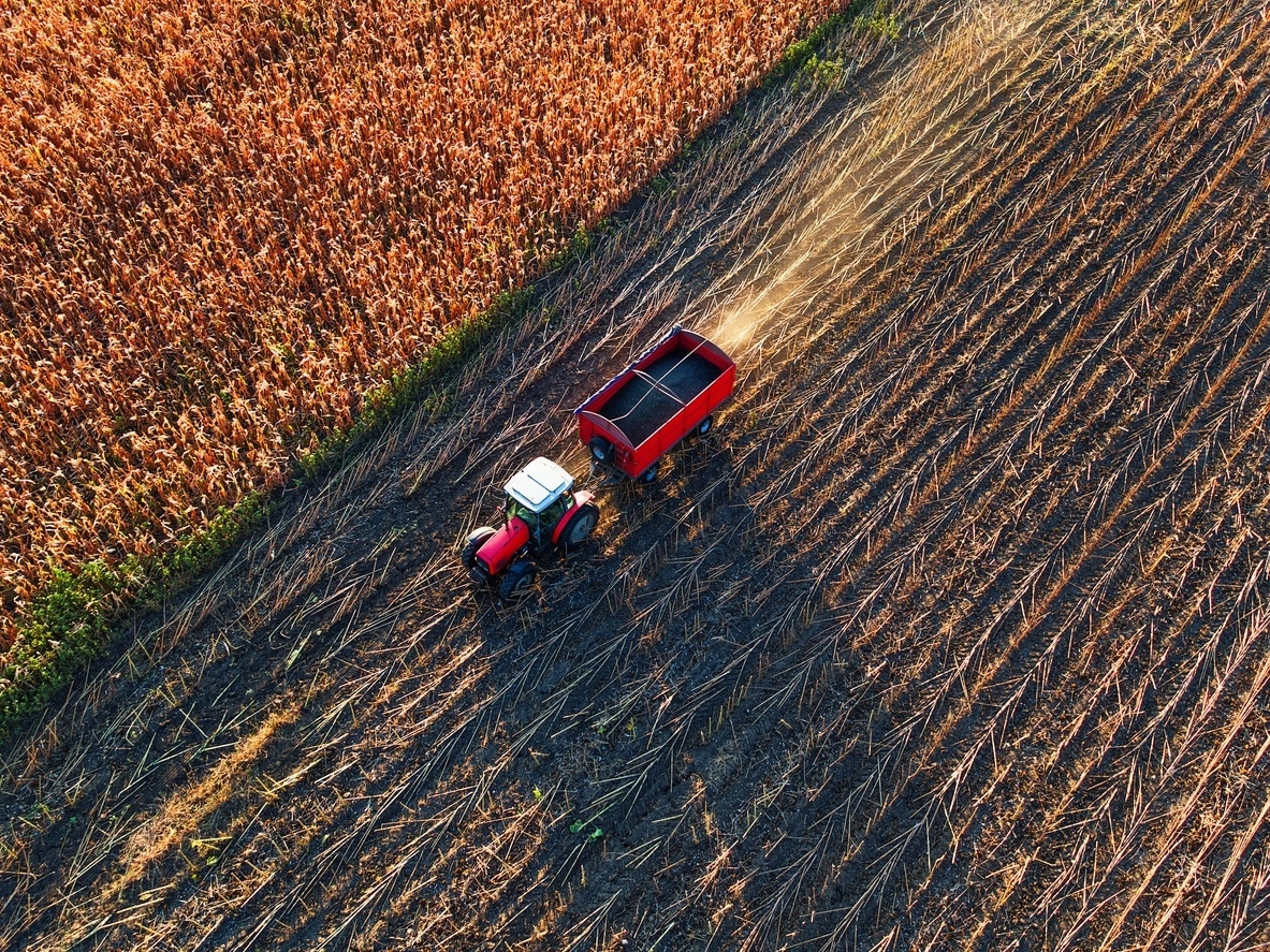 Aerial view of farmer driving agricultural tractor and trailer full of grain